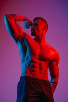 Un bodybuilder con la barba posa con un bicipite flesso sotto la luce blu e rossa