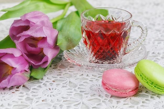 Tazza trasparente in cristallo di boemia di tè rosso karkadeh con biscotti, macarons e tulipani perple su una bellissima tovaglia all'uncinetto