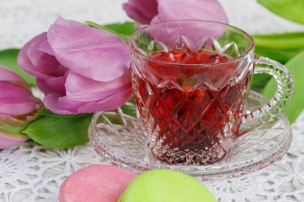 Tazza trasparente in cristallo di boemia di tè rosso karkadeh con biscotti, amaretti e tulipani viola su una bellissima tovaglia all'uncinetto