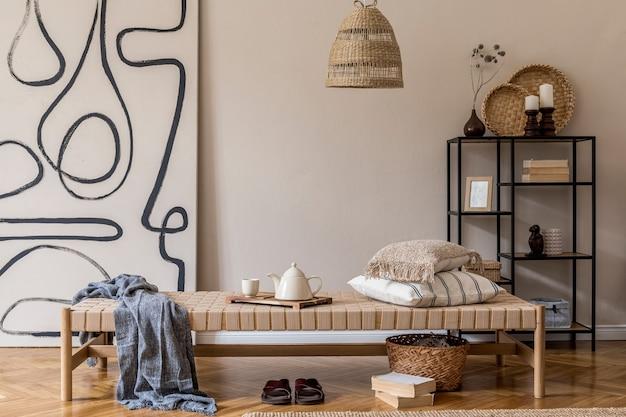 Composizione boho del soggiorno con mobili, quadri, decorazioni in rattan ed eleganti accessori personali.