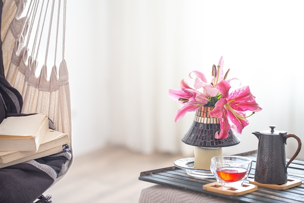 Sedia pensile in stile boho con una pila di libri. vassoio in legno con teiera e tazza di tè e bellissimi fiori di giglio.