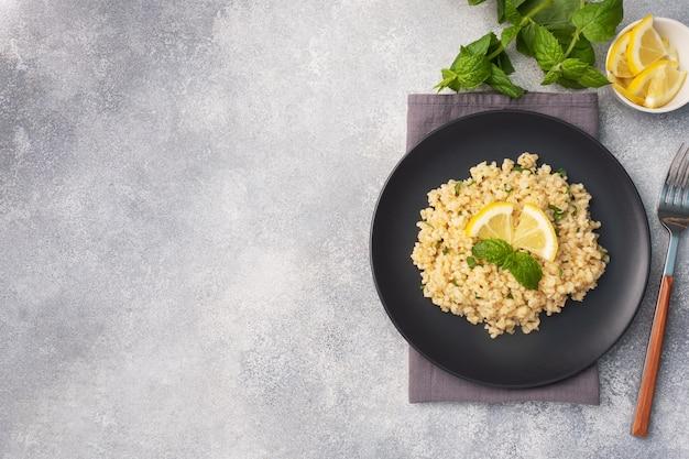 Bulgur bollito con limone fresco e menta su un piatto. un piatto tradizionale orientale chiamato tabouleh. vista dall'alto di sfondo grigio cemento, copia spazio