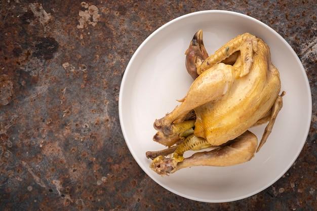 Pollo bollito in un semplice piatto di ceramica su sfondo arrugginito con copia spazio per il testo, vista dall'alto