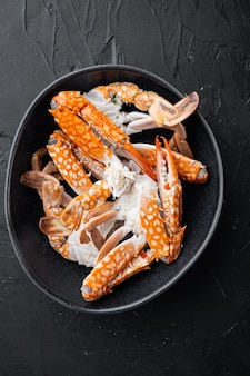 Set di cibo di granchio bollito, su sfondo nero, vista dall'alto laici piatta