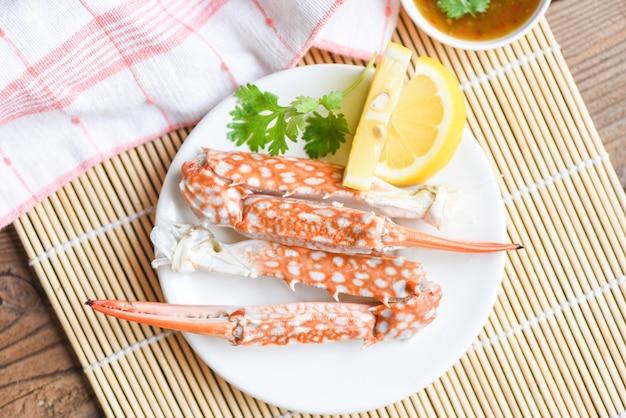 Cibo di granchio bollito sul piatto bianco e salsa di frutti di mare sul tavolo