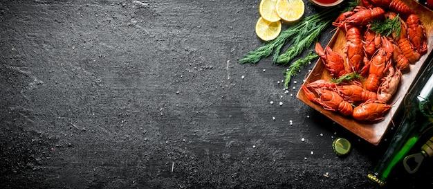Gamberi bolliti con birra, fette di limone e aneto. su sfondo nero rustico