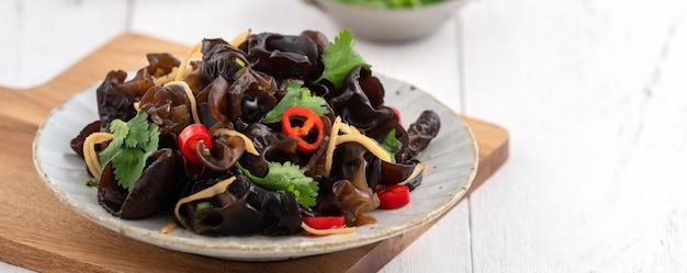 Fungo nero commestibile bollito dell'albero, orecchio di legno in un piatto sulla superficie bianca della tavola