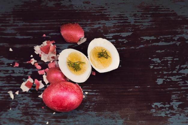 Uovo sodo tagliato a metà sdraiato sul vecchio tavolo blu. sfondo vintage dipinto. colazione in occasione della celebrazione della domenica di pasqua