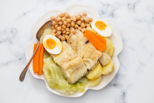 Pesce bollito con verdure e uovo sodo sul piatto bianco