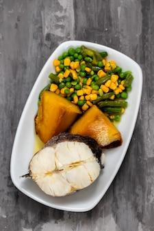 Pesce bollito con verdure sul piatto bianco