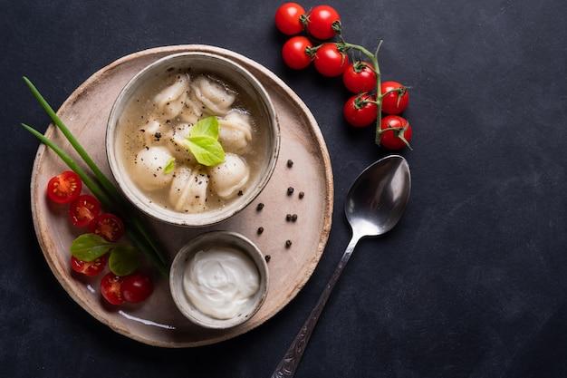 Gli gnocchi bolliti della carne sono servito con panna acida e i pomodori ciliegia su fondo rustico. pelmeni russo tradizionale. vista dall'alto.