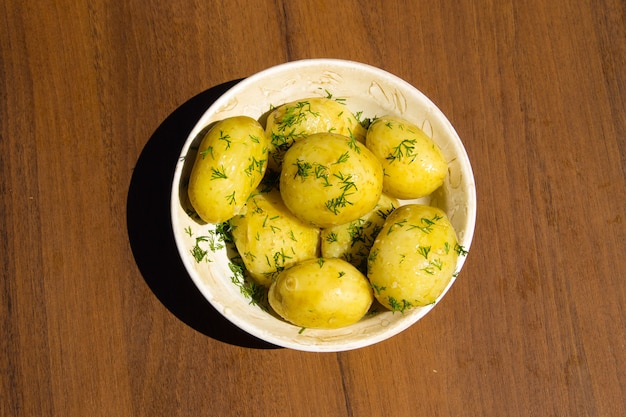 Patate novelle bollite con burro e aneto sulla tavola di legno. vista dall'alto