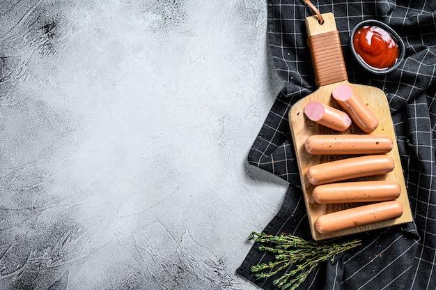 Salsicce di maiale bollite classiche su un tagliere con rosmarino e spezie. sfondo nero. vista dall'alto. copia spazio