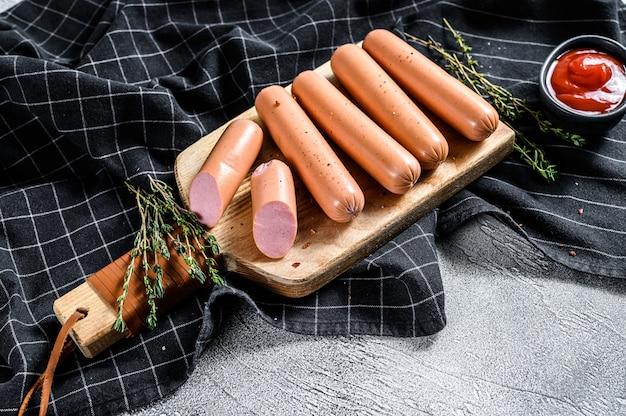 Salsicce di maiale bollite classiche su un tagliere con rosmarino e spezie. sfondo nero. vista dall'alto