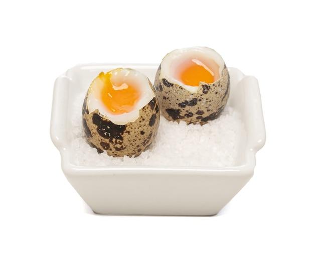 Uova di quaglia bollite in un piattino su una superficie bianca