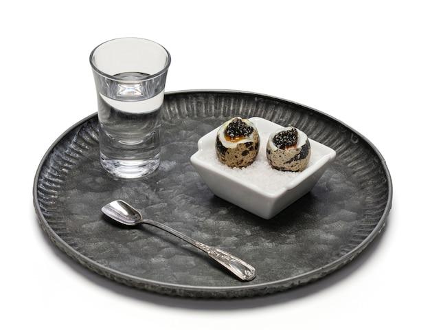 Uova di quaglia bollite con caviale e un bicchiere di vodka su bianco
