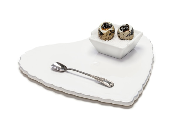 Uova di quaglia bollite con caviale su sfondo bianco