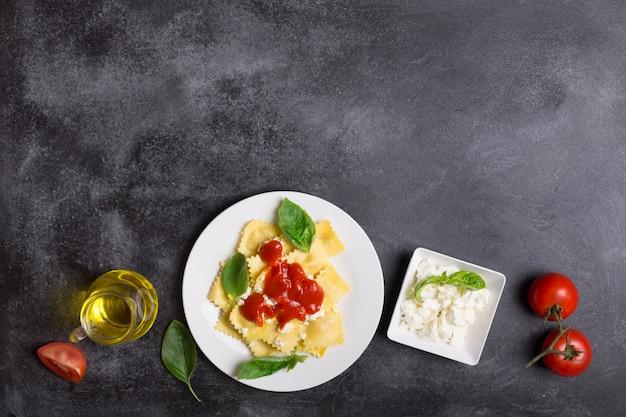 Ravioli bolliti con basilico, formaggio e salsa di pomodoro su uno sfondo nero