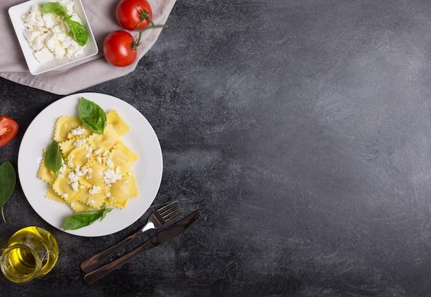 Ravioli bolliti con basilico, formaggio e pomodori su sfondo nero