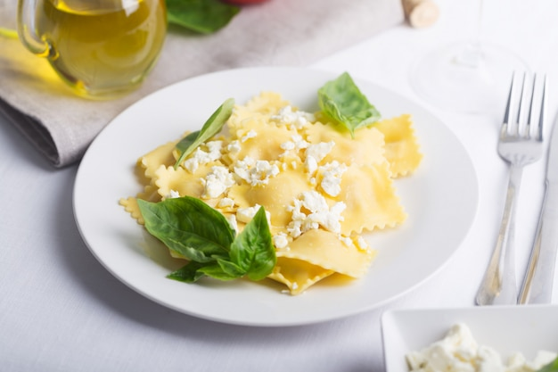 Ravioli bolliti con basilico, formaggio e pomodori sulla tavola bianca