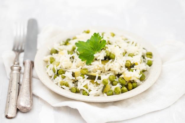 Riso bollito con verdure verdi nel piatto