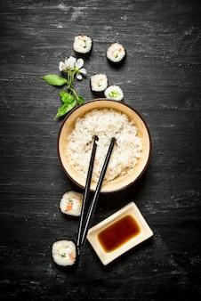 Riso bollito con involtini primavera e salsa di soia. su uno sfondo di legno nero