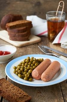 Salsiccie bollite con piselli in scatola su un piatto