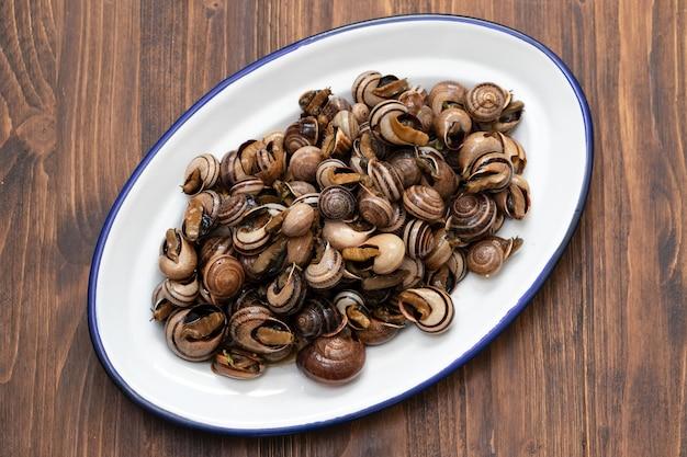 Lumache bollite con erbe nel piatto bianco su fondo in legno Foto Premium