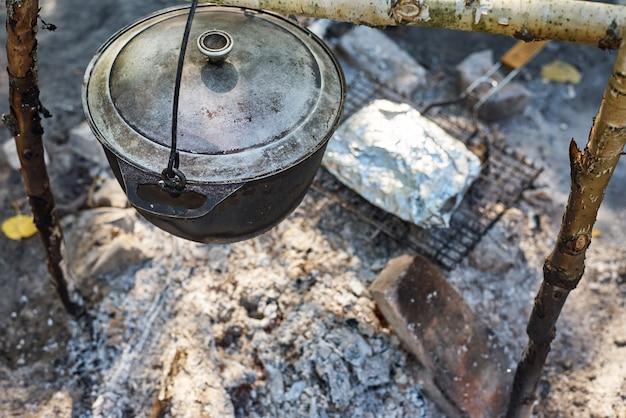 Pentola bollente al fuoco sul picnic. concetto di cucina escursionistica