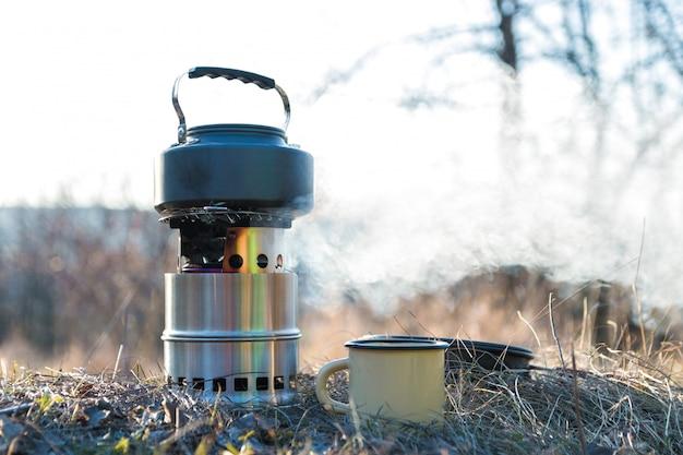 Acqua bollente in bollitore sul bruciatore a legna portatile con fumo. preparazione del tè all'aperto