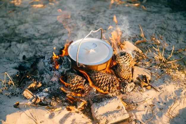 Acqua bollente in vaso di metallo all'aperto. preparazione del tè in natura selvaggia in campeggio. attrezzatura turistica.