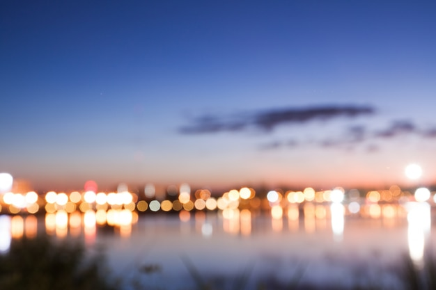 Bokeh della luce della città con vista sul lago, sfondo sfocato nella natura