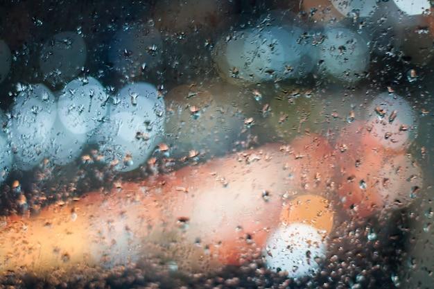 Luci bokeh sulla pioggia guardano fuori dalla finestra.