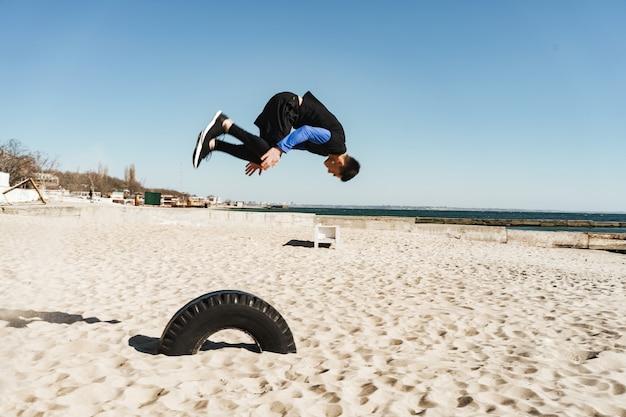Ragazzo audace ventenne in tuta nera che fa parkour e salta durante le acrobazie mattutine in riva al mare