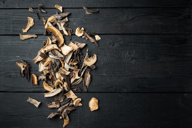 Boletus funghi secchi selvatici insieme, su fondo di tavolo in legno nero, vista dall'alto piatto laici,