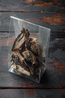 Boletus funghi secchi selvatici insieme, sul vecchio fondo di tavolo in legno scuro, in confezione di plastica