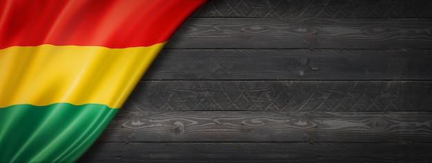 Bandiera della bolivia sul muro di legno nero. banner panoramico orizzontale.