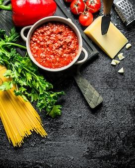 Ragù alla bolognese in padella con pasta secca e formaggio. su sfondo nero rustico