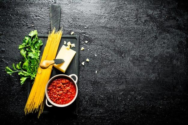 Sugo alla bolognese con pasta secca ed erbe aromatiche. su sfondo nero rustico