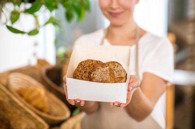 Buon appetito. mani pulite delle donne che tengono fuori la scatola dei panini appetitosi freschi che offrono ossequi