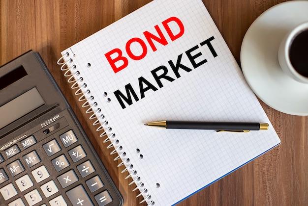 Bond market scritto in un blocco note bianco vicino a una calcolatrice e una tazza di caffè su uno sfondo di legno scuro