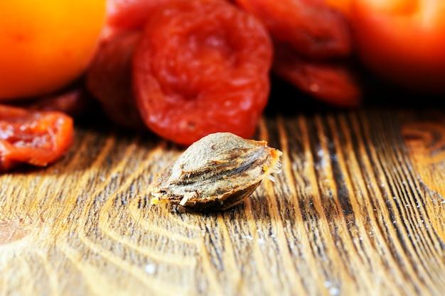 Un osso di albicocca che giace con albicocche fresche e mature e secche su un tavolo di legno