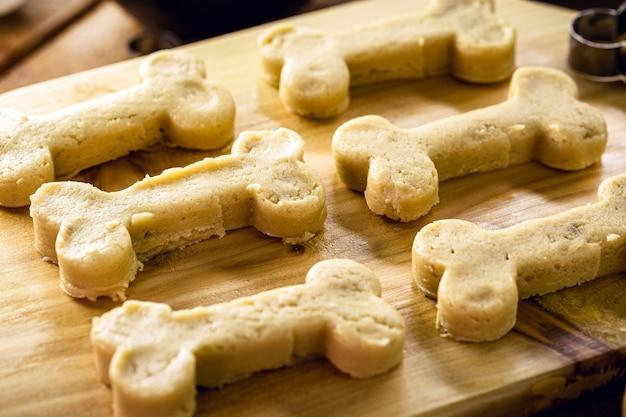 Biscotto a forma di osso che sta per essere cotto, pasta cruda, merenda per animali fatta in casa