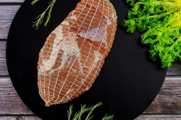 Arrosto di spalla di maiale disossato sulla tavola di legno. avvicinamento.