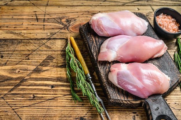 Filetto di coscia di pollo crudo disossato. fondo in legno. vista dall'alto. copia spazio.