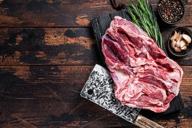 Cosciotto di montone crudo disossato carne di agnello su tagliere da macellaio con mannaia