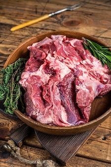 Carne di spalla di agnello di montone crudo disossato in piatto di legno con erbe aromatiche
