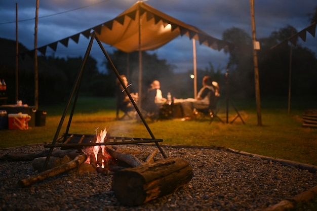 Falò vicino alla tenda da campeggio all'aperto con persone sedute in sottofondo la sera.