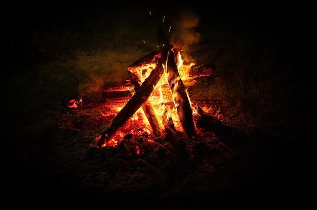 Falò. falò di notte isolato sul nero. tronchi e legna da ardere. falò di notte. ceppi che bruciano nel fuoco da campo al buio
