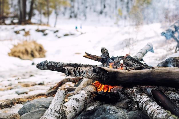 Falò accatastati sulle rocce sullo sfondo della foresta invernale da vicino